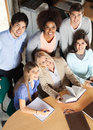 Teacher and students with books smiling in high angle portrait of mature together at desk classroom Royalty Free Stock Photos