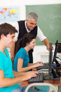 Teacher students computer cheerful middle aged helping high school with work Royalty Free Stock Photography