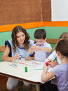 Teacher with students painting at desk young in kindergarten Royalty Free Stock Photos