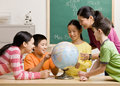 Teacher and students viewing globe in classroom