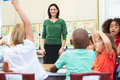Teacher talking to elementary pupils in classroom raising arm Stock Photos