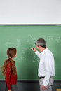 Teacher teaching mathematics to teenage schoolgirl side view of male in classroom Stock Photos