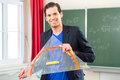 Teacher with triangle in front of a school class or docent holding geometry blackboard Royalty Free Stock Image
