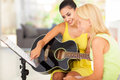 Teacher tutoring girl pretty music young to play guitar Stock Photography