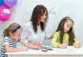 Teacher with two girls in kindergarten Stock Photos