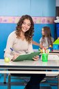 Teacher writing in book beautiful young with student playing background at kindergarten Royalty Free Stock Photo