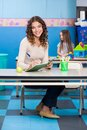 Teacher writing in book with girl playing in full length portrait of young background at kindergarten Royalty Free Stock Photography