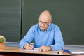 Teacher writing notes at his desk mature male sitting in front of the chalkboard Stock Photos