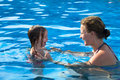 Teaching daughter how to swimm mother her by not scare of water Stock Photos