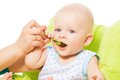 Teaching to eat from the spoon cute little baby boy Stock Image