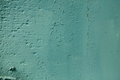 Teal color rough textured painted wall background