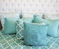 Teal cushions and bedding textiles Stock Images