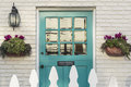 Teal front door of a classic home wooden to with white picket fence gate in foreground the is framed by two flower planters and Stock Images