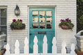 Teal front door of a classic home wooden to with white picket fence gate in foreground the is framed by two flower planters and Royalty Free Stock Photography