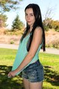 Teal tee pretty young brunette in a shirt and denim shorts Stock Photography