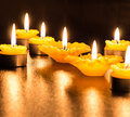 Tealight candles multiple at night on table Royalty Free Stock Photos