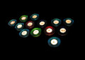 Tealights with colorful holders in blue turquoise green and red isolated on black Royalty Free Stock Photography