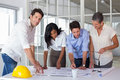 Team of architects going over blueprints with one smiling at camera Royalty Free Stock Photo