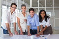 Team of architects going over blueprints smiling at camera Royalty Free Stock Photo