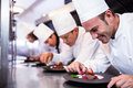 Team of chefs finishing dessert plates in the kitchen Royalty Free Stock Photo