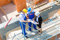 Team discussing construction or building site plans architect and builder worker with helmets discuss on a scaffold plan blueprint Royalty Free Stock Photo