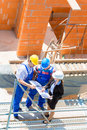 Team discussing construction or building site plans architect and builder worker with helmets discuss on a scaffold plan blueprint Royalty Free Stock Images