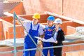 Team discussing construction or building site plans architect and builder worker with helmets discuss on a scaffold plan blueprint Stock Photography