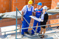 Team discussing construction or building site plans architect and builder worker with helmets discuss on a scaffold plan blueprint Royalty Free Stock Image