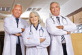 Team of doctors in hospital three smiling with their arms crossed a Royalty Free Stock Images