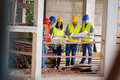 Team of experts studying blue print at construction site Royalty Free Stock Photo