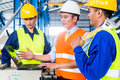 Team in factory at production training of workers and engineer with laptop Stock Photo