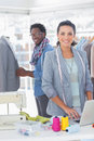 Team of fashion designers working and smiling at camera Royalty Free Stock Photo