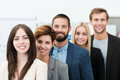 Team leadership conceptual image of with a group of professional successful young business men and women standing in a line headed Stock Photos