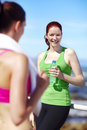 Team meeting two young healthy woman having a conversation while jogging Stock Images