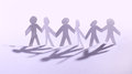Team of paper doll people holding hands Stock Photo