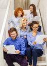 Team with papers and take away coffee on staircase business office startup concept smiling creative Royalty Free Stock Photography
