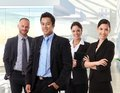 Team portrait of happy business people interracial standing in office lobby smiling Stock Photos