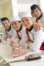 Team of students in butchery happy young butchers school kitchen Stock Images