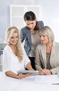 Team successful business team of woman in the office talking to women together looking at tablet computer Stock Photos