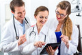Team of young doctors in clinic with tablet computer male and female discussing test reports that show on their Royalty Free Stock Images