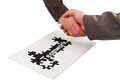 Teamwork concept handshaking and puzzle as Stock Images