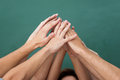 Teamwork and cooperation with a group of young people all raising their hands together forming an overlapping pyramid closeup Stock Photography