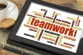 Teamwork word cloud on a digital tablet with a cup of coffee Stock Photos