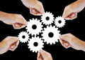 Teamwork works together to build a cog wheel gear system. Royalty Free Stock Photo