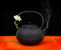Teapot with chamomile flower and smoke on tabletop Royalty Free Stock Photos