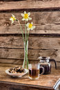 Teapot, cup of tee, plate with cookies and a vase with daffodil flowers  on a table against the background of the wooden walls Royalty Free Stock Photo