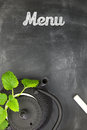 Teapot with fresh herbs on chalkboard top shot copy space Stock Photo