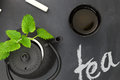 Teapot with fresh herbs and teacup on chalkboard top shot Royalty Free Stock Images