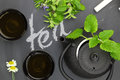Teapot with fresh herbs and teacups on chalkboard top shot Royalty Free Stock Images