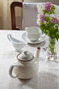 Teapot milk jug and teacup a tea cup on saucer flowers in a vase Royalty Free Stock Photos